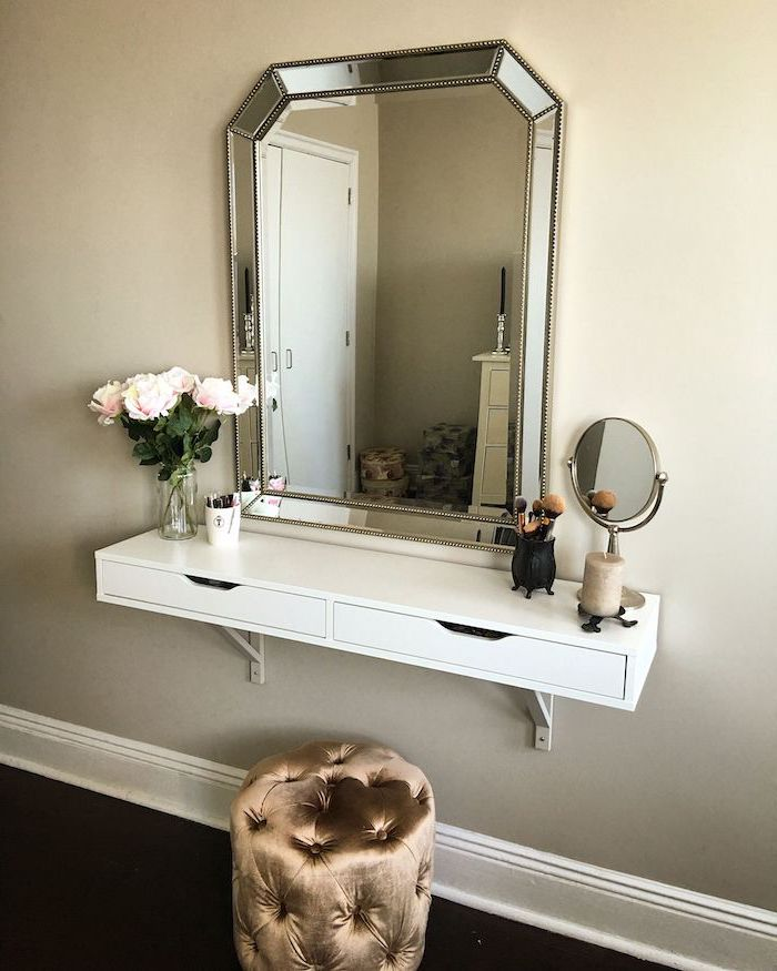 dressing table mirror, floating white shelf, brown velvet ottoman, white wall, roses bouquet
