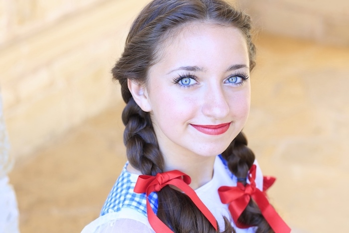 dorothy braids, triangle box braids, red bows, two braids, blue eyes, red lipstick