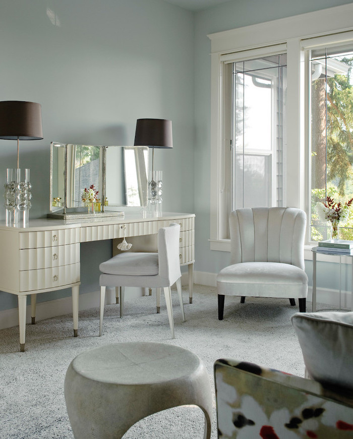 white table with drawers, three fold mirror, white chair, white velvet armchair, makeup vanity with lights