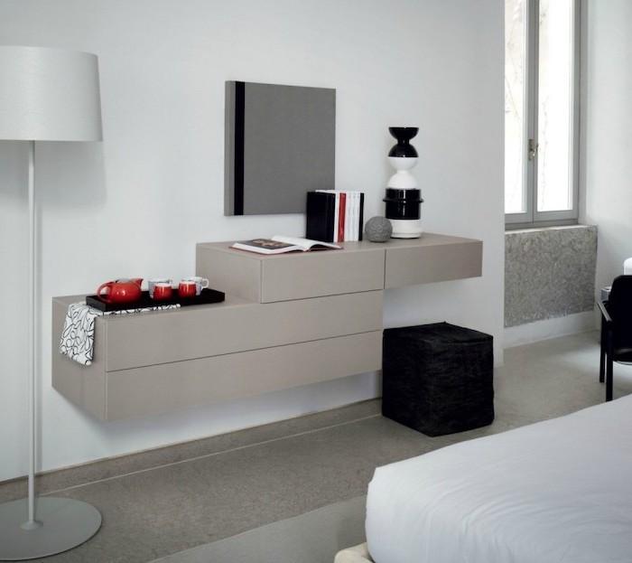 white wall, floating shelves, dressing table mirror, black ottoman, tea set, square mirror
