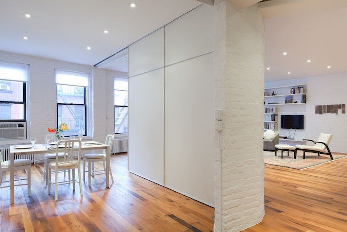 white brick wall, wooden floor, wooden room dividers, white panels, white chairs, dining table