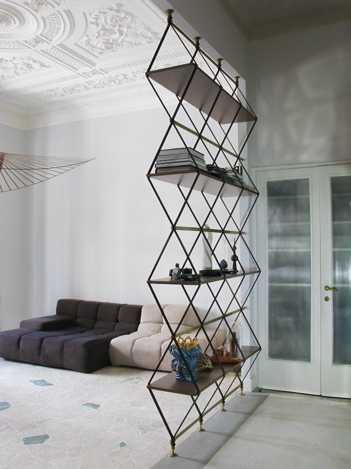 metal triangles and bookshelves, hanging room dividers, white carpet, black and white sofa