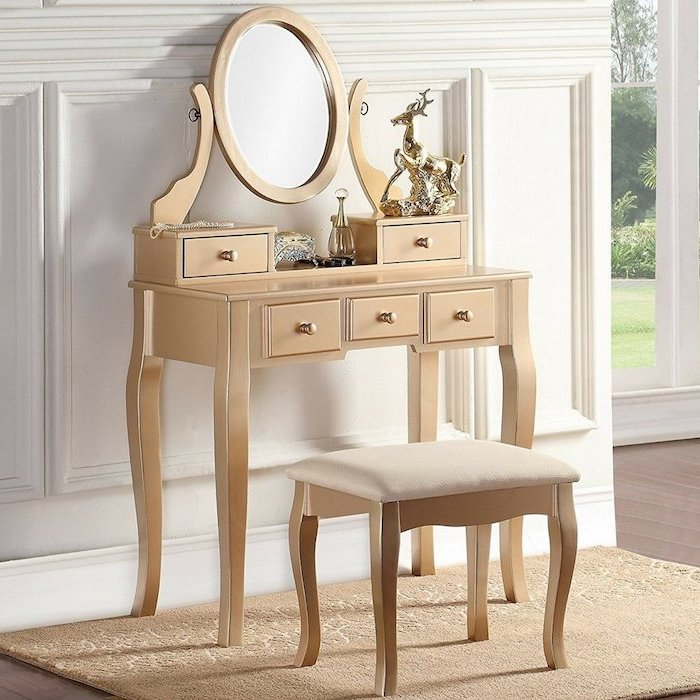 gold metal, makeup vanity, gold stool, gold rug, white wall, wooden floor, small mirror