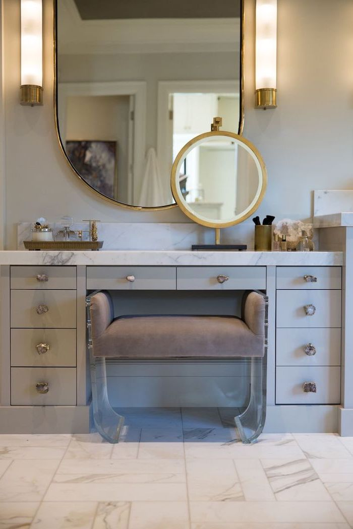 mirrored vanity table, grey drawers, marble countertop, grey velvet ottoman, tiled marble floor