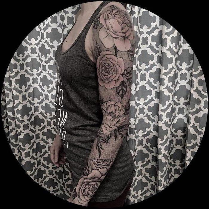 floral tattoo, grey top, grey background, dragon sleeve tattoo