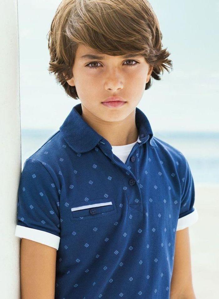 little boy, wearing a blue shirt, brown hair, medium length, short guy haircuts