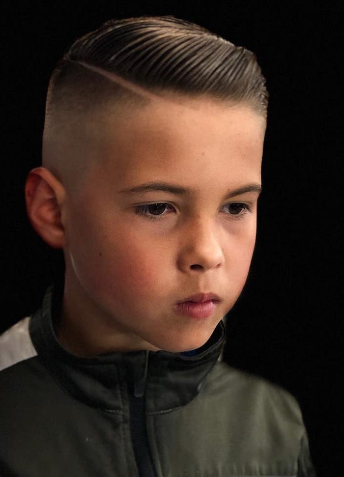 black background, olive green jacket, long hairstyles for boys, dark blonde hair