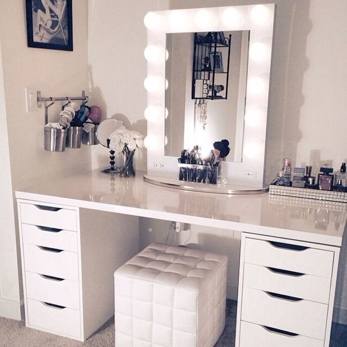mirror with lights, white leather ottoman, makeup vanity chair, white drawers, tray full of perfumes