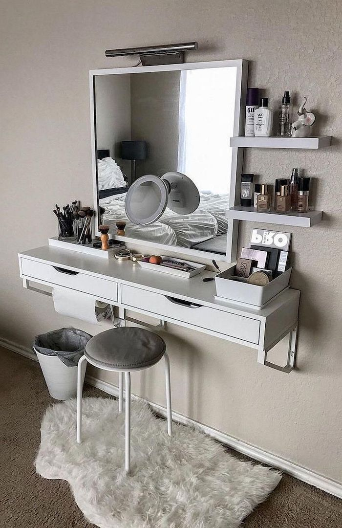 white floating shelf, with drawers, white metal stool, mirrored vanity table, white wall, white rug