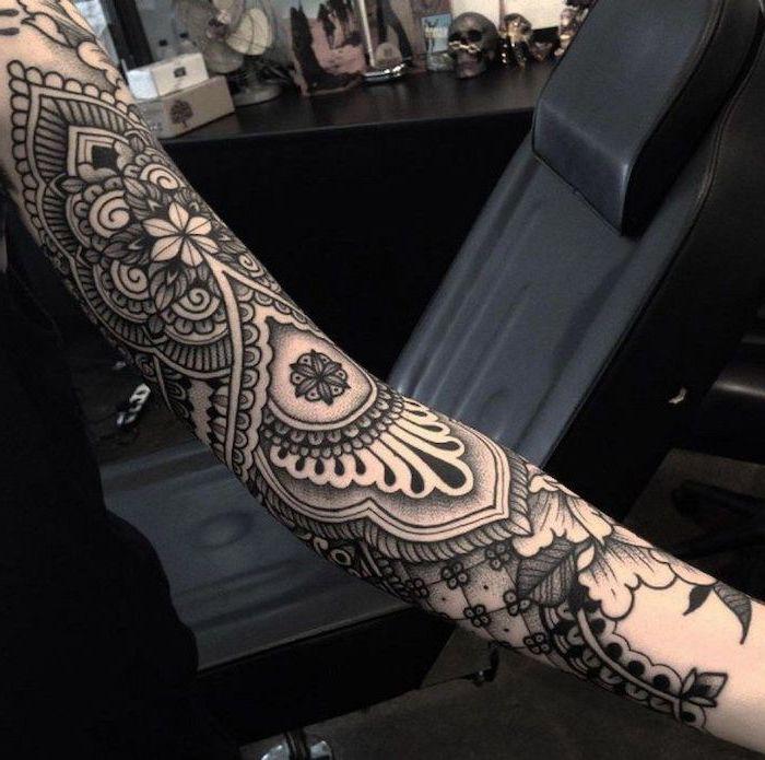 mandala tattoo, black leather armchair, black top, skull sleeve tattoo