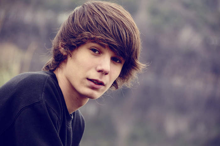 long hairstyles for boys, black blouse, brown hair, blurred background