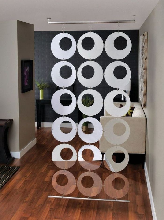 metal round blocks, arranged together, panel room divider, wooden floor, white sofa, black brick wall