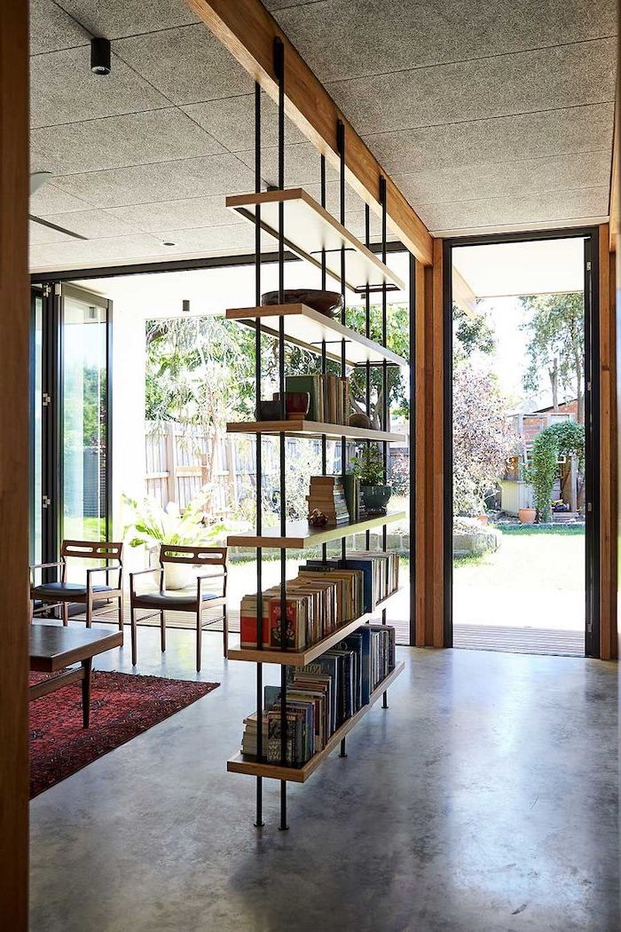 room divider shelves, wooden bookcase, cement floor, tall windows, red carpet, wooden chairs