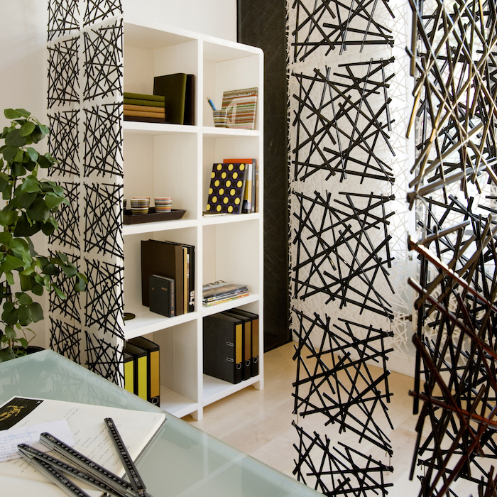 black metal sticks, arranged together in square blocks, room divider shelves, white bookcase, glass desk