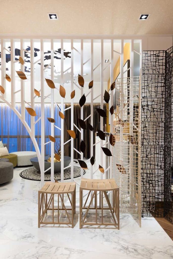 white poles, golden leaves, marble floor, room divider shelves, wooden stools