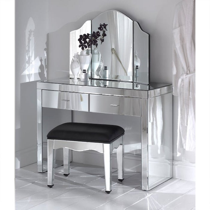 mirrored table, black leather stool, three fold mirror, white makeup vanity, white wall, tiled floor