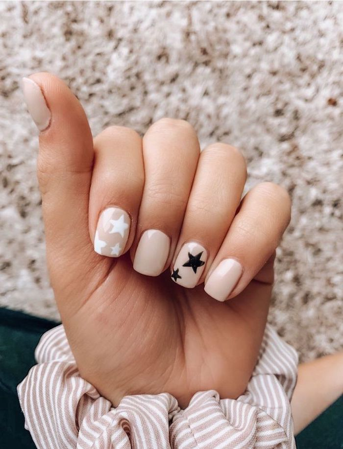 nude nail polish, black and white stars, nail color ideas, blurred background