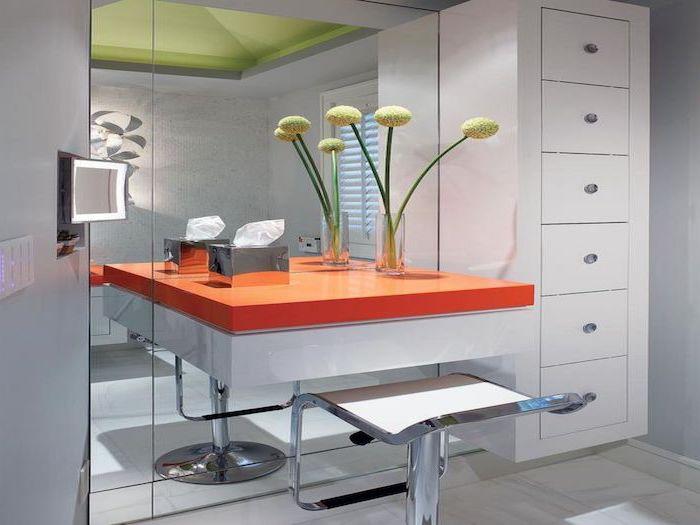 orange floating shelf, metal stool, small makeup vanity, white drawers, large mirror