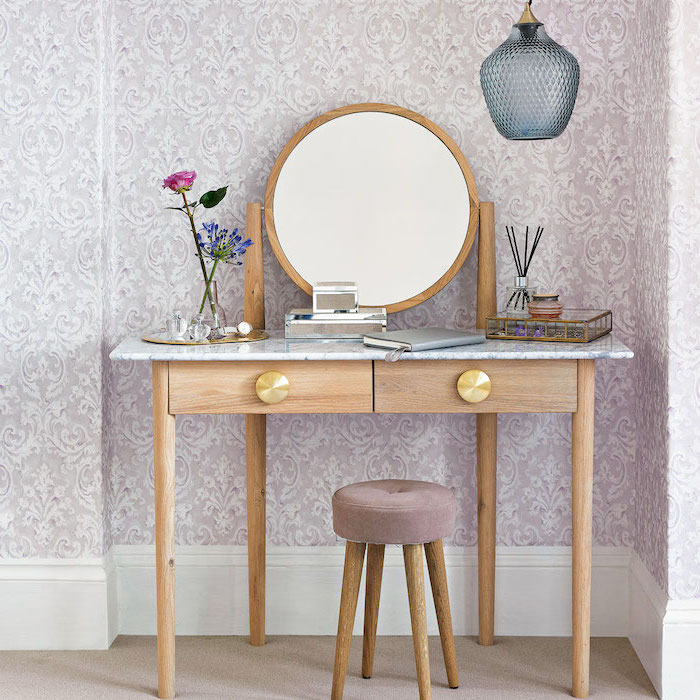 white makeup vanity, wooden table with drawers, marble countertop, grey velvet stool, round mirror