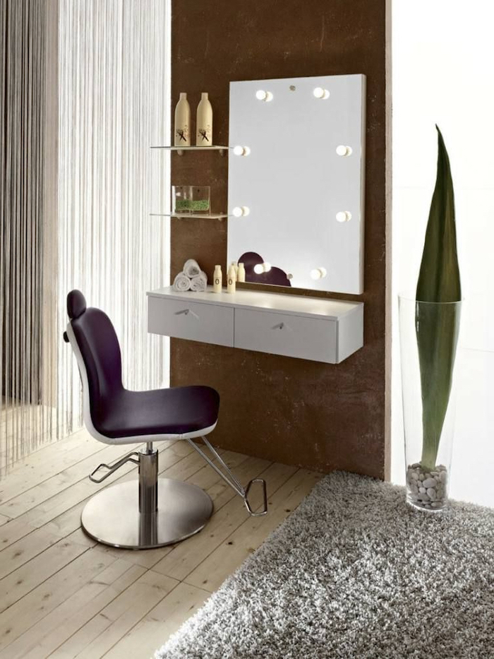 mirror with lights, purple leather chair, wooden floor, grey carpet, small makeup vanity, white floating shelf
