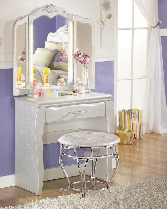 purple walls, white leather table, with drawer, three fold mirror, small makeup vanity, white leather stool