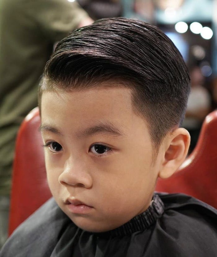 little boy, in a red chair, side swept, black hair, types of haircuts for men, black eyes