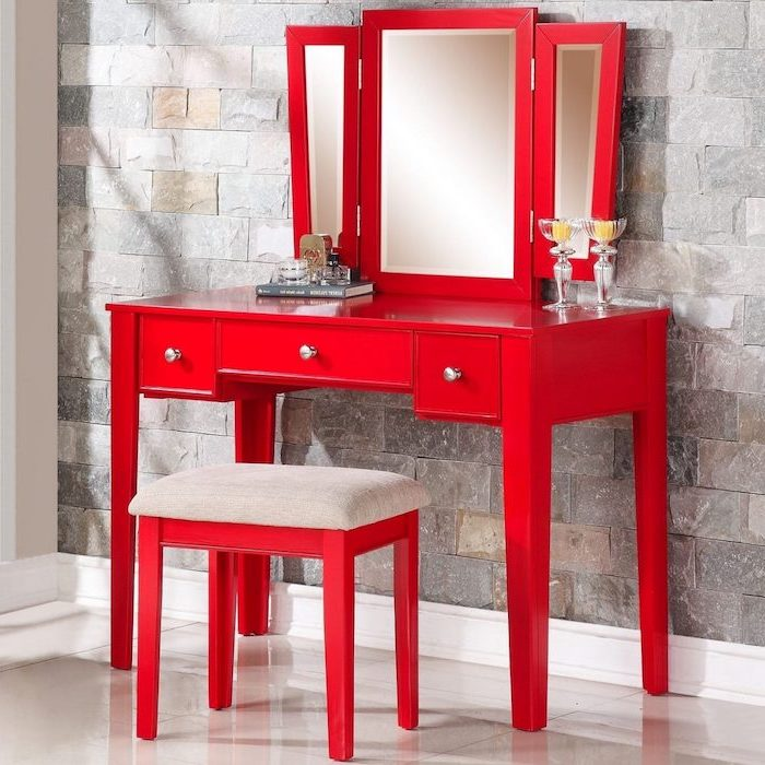 corner makeup vanity, red wooden table, red wooden stool, three fold mirror, stone wall