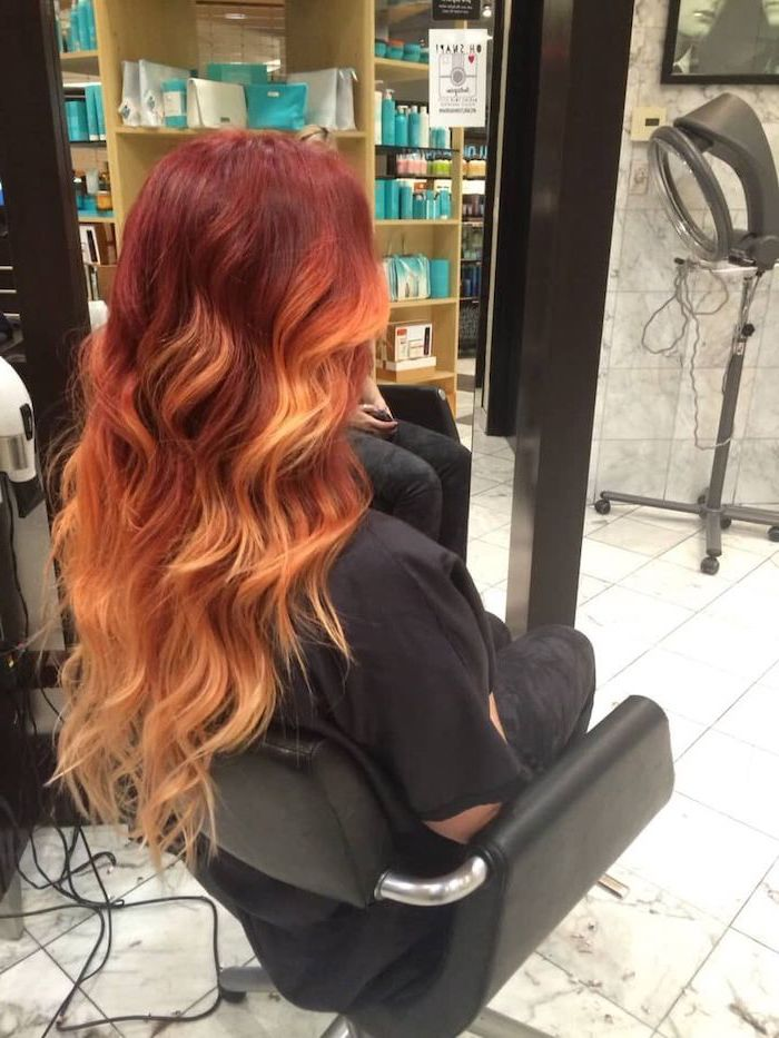 dark to light red, long wavy hair, black leather chair, black shirt, rose gold ombre hair