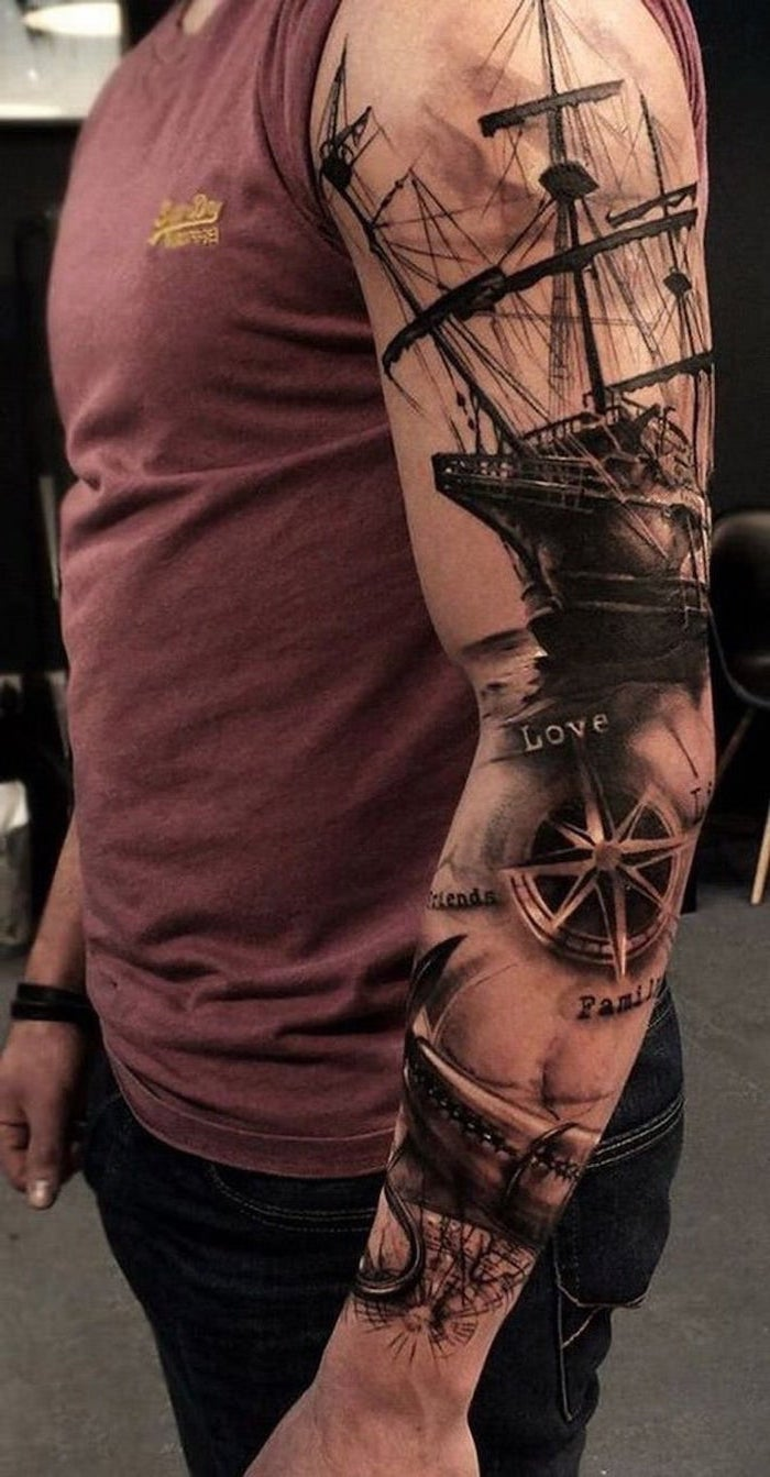 red top, forearm sleeve tattoo, black jeans, ship and compass