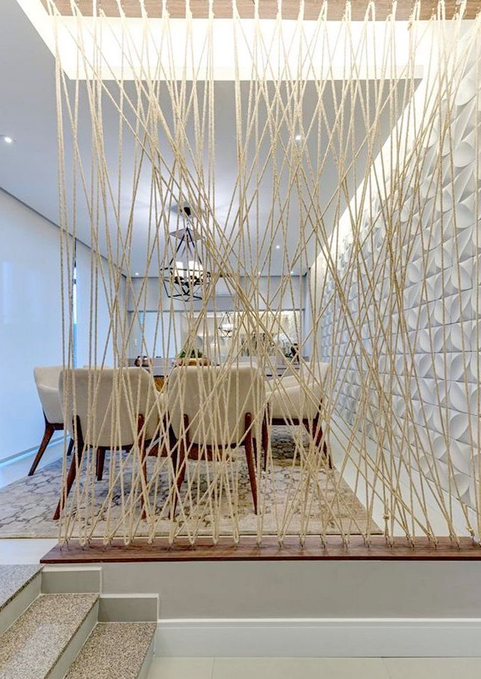 white ropes, white chairs, room divider bookcase, white wall, dining table