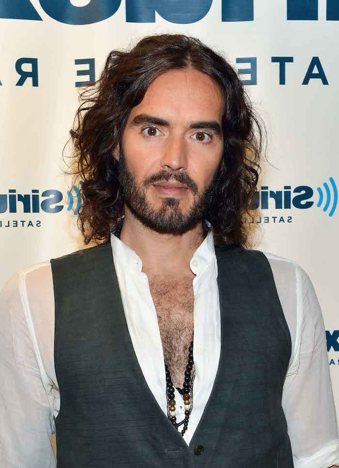 russell brand, medium length hair men, white shirt, grey vest, brown curly hair