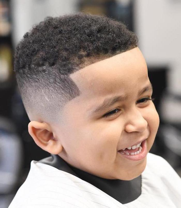 cool guy haircuts, black curly hair, little boy smiling, blurred background