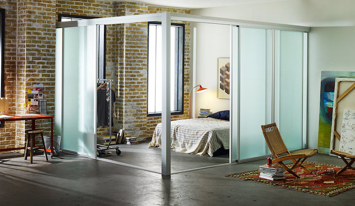 frosted glass, sliding panels, room divider bookcase, wooden armchairs, brick wall, cement floor