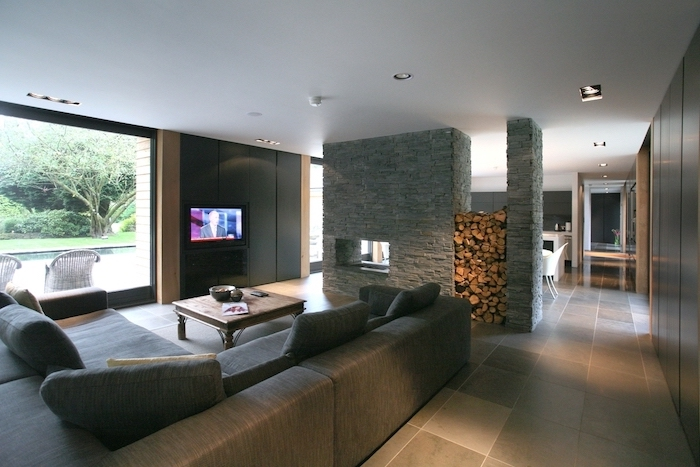 stone wall and wood, grey corner sofa, room separator, tiled floor, wooden table, black walls
