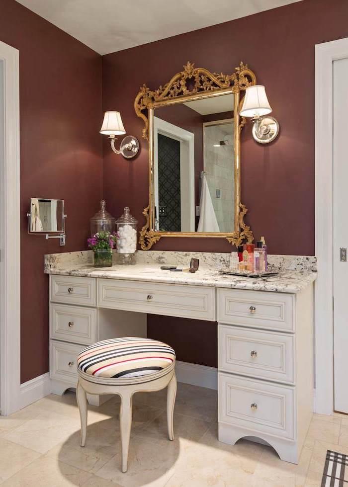 dark red walls, vintage mirror, white table, with drawers, marble countertop, corner makeup vanity