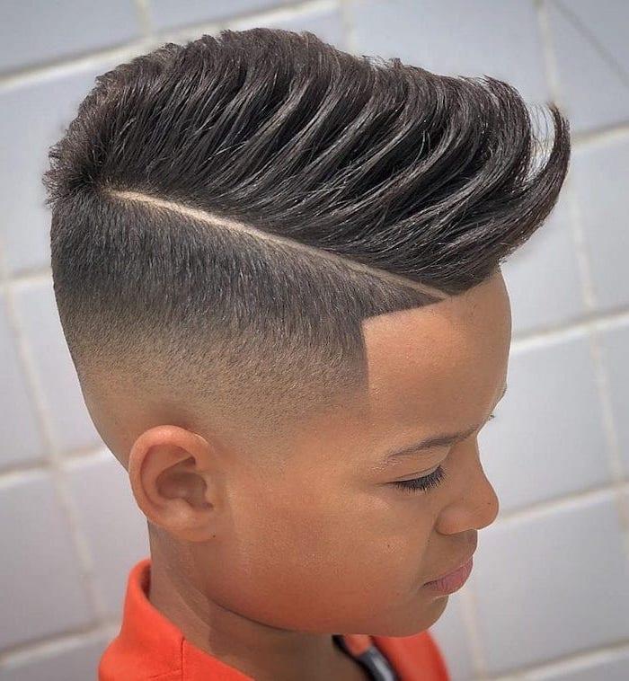 black hair, side swept, cool hairstyles for men, tiled wall, orange shrit