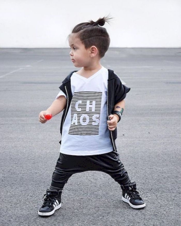 little boy, short guy haircuts, brown hair, in a bun, black leather pants, white shirt, black vest, black sneakers