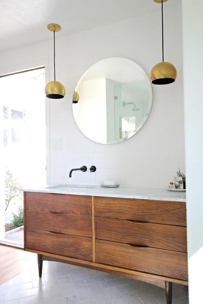 round mirror, white makeup vanity, wooden table with sink, marble countertop, white wall