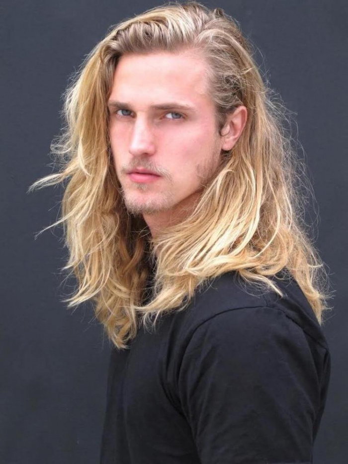 blonde wavy hair, hairstyles for men with thick hair, black shirt, grey background
