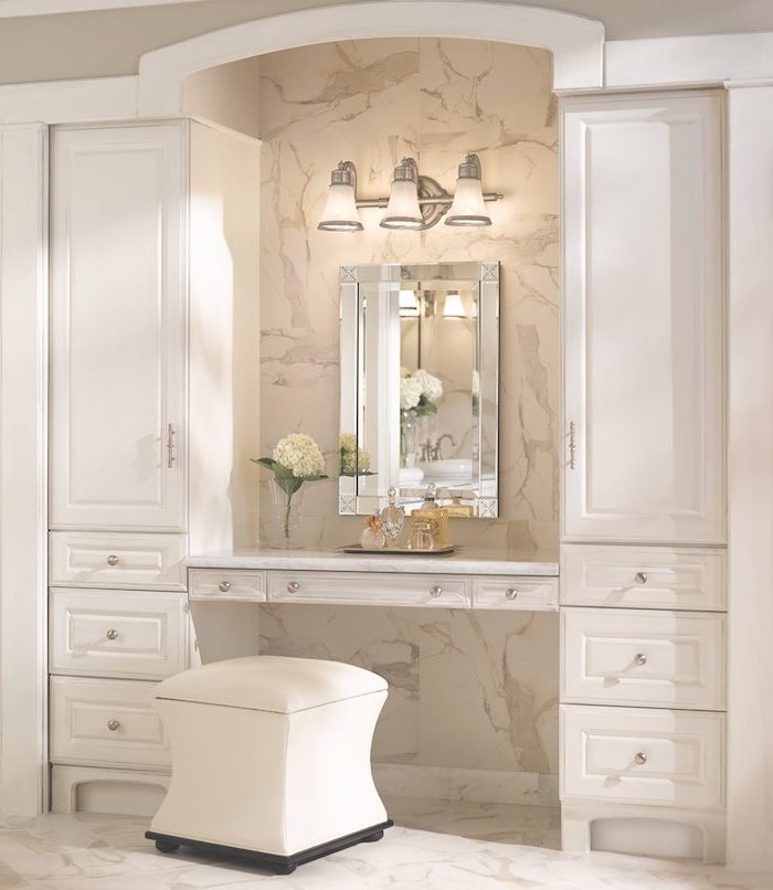 tiled marble wall and floor, white leather ottoman, makeup vanity table with lighted mirror, white drawers