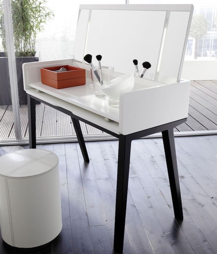 wooden floor, white leather ottoman, makeup vanity table with lighted mirror, pull out mirror