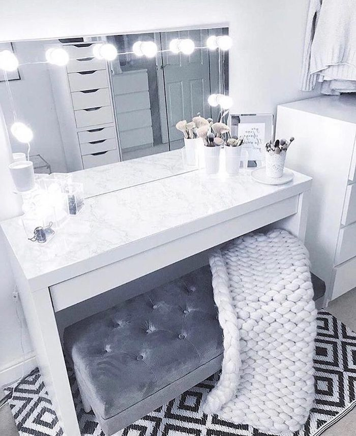 grey velvet ottoman, white knitted blanket, modern makeup vanity, marble countertop, mirror with lights