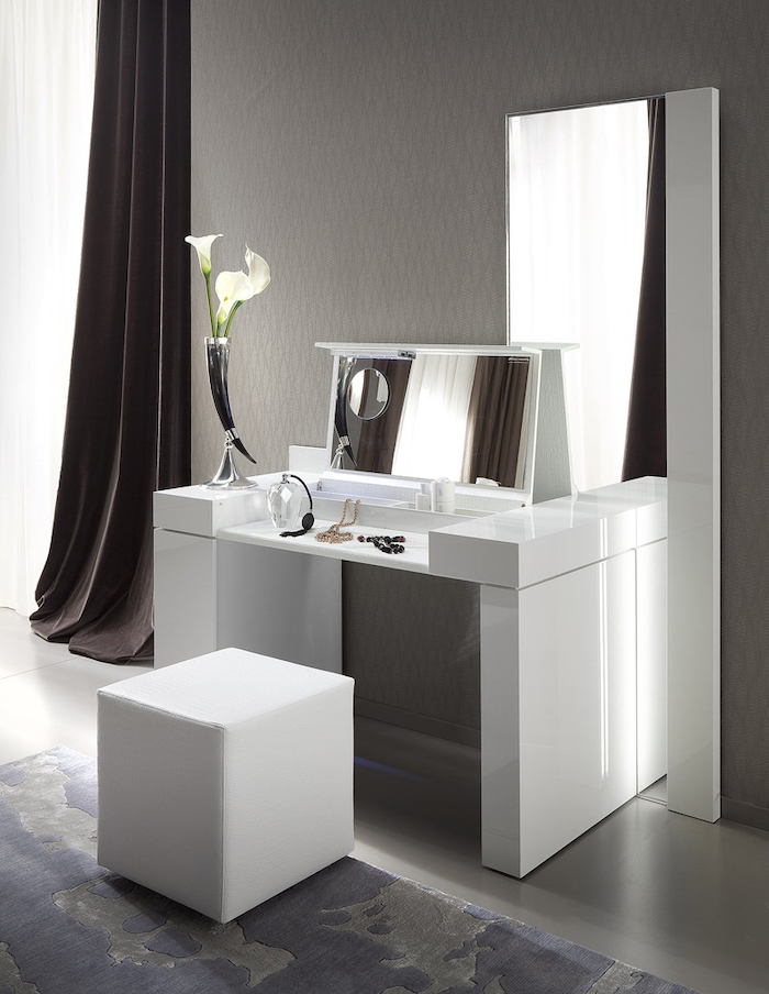 makeup vanity, white table, pull out mirror, white leather ottoman, grey and blue carpet, grey walls