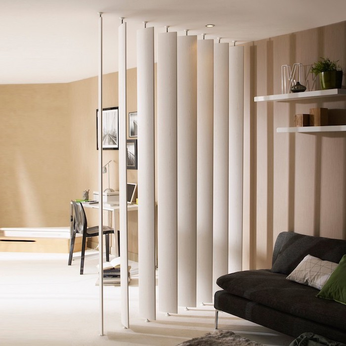 folding screen room divider, white panels, black sofa, desk and chair, white floor, beige walls