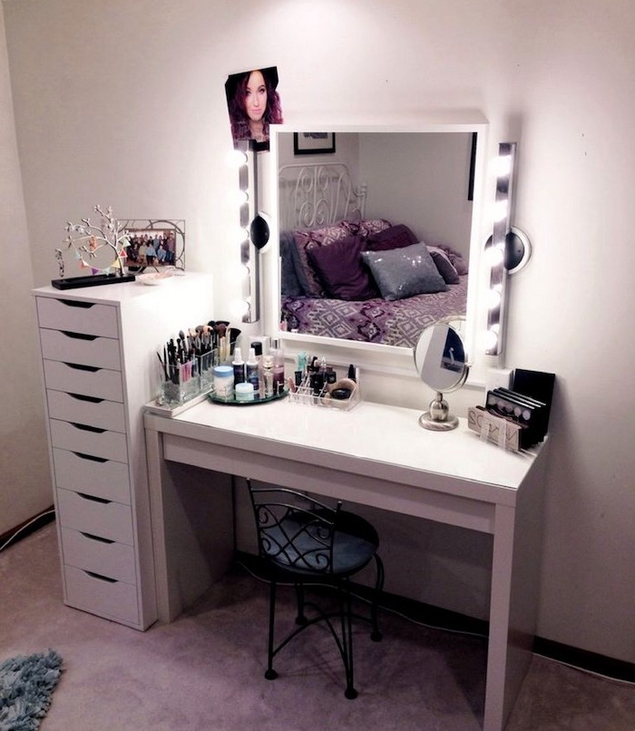 white drawers, black metal chair, bathroom makeup vanity, mirror with lights, white wall