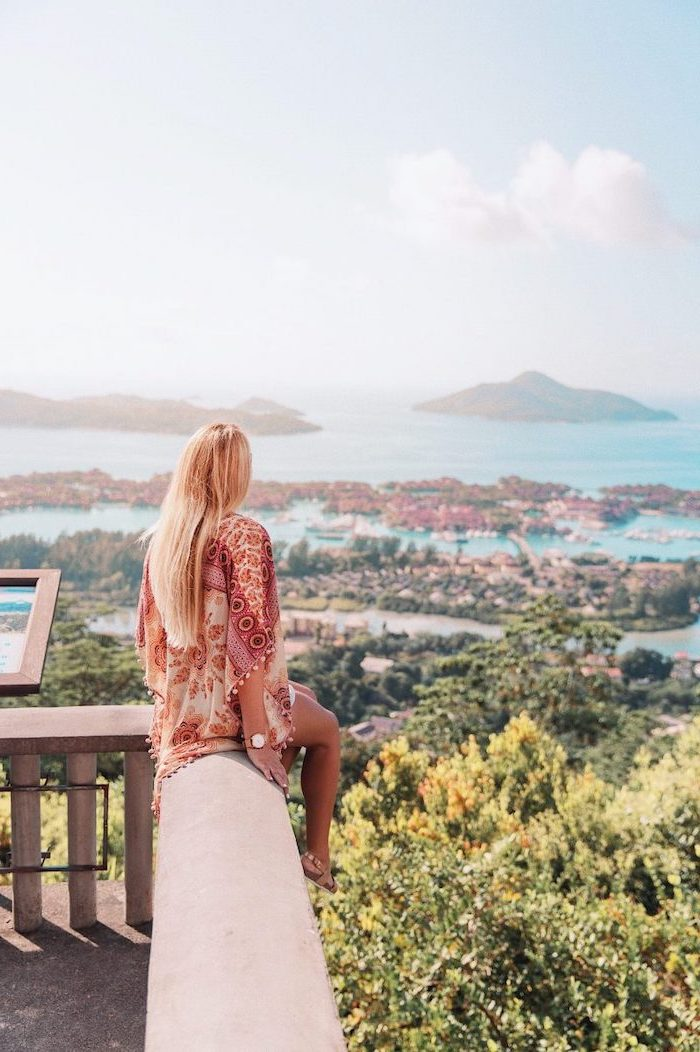 woman sitting on a balcony, with a blonde hair, overlooking the island, seychelles islands