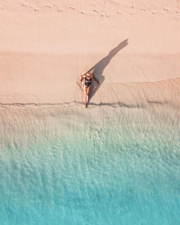 woman sitting on the beach, beach sand, blue water, black swimsuit, digital nomad, seychelles islands