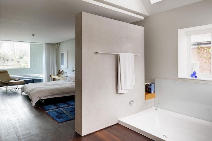 wooden floor, sinking bathtub, indoor privacy screen, separating bedroom and bathroom