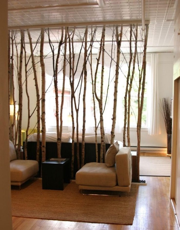 indoor privacy screen, made of tree branches, white armchairs, wooden floor, beige carpet