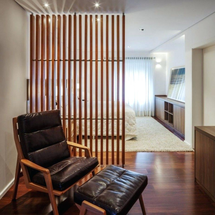 wooden poles, portable room dividers, black leather armchair, wooden floor, white carpet